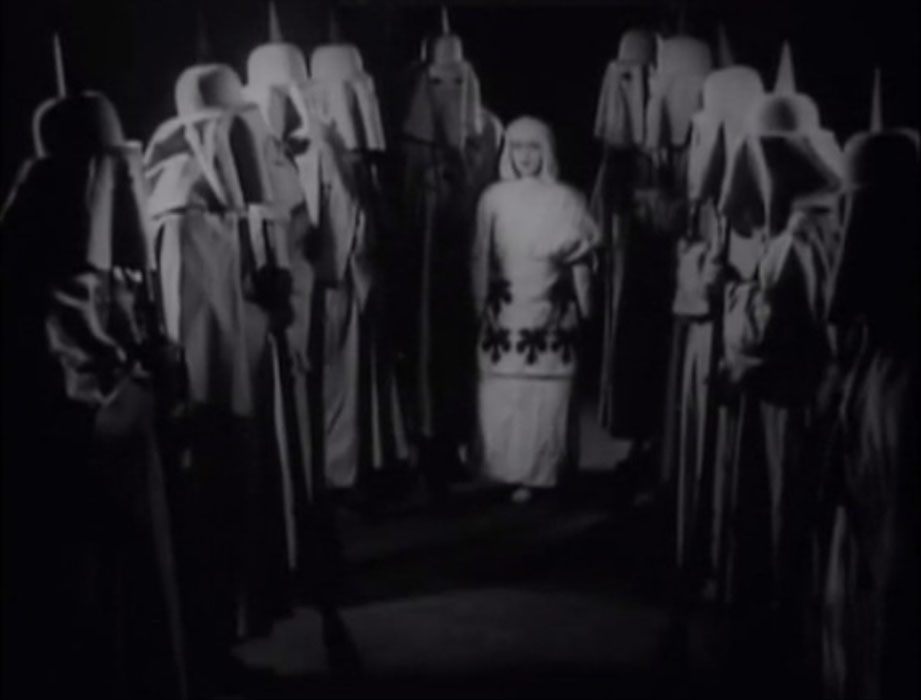 A woman in white is surrounded by hooded Danites in A Mormon Maid (1917).